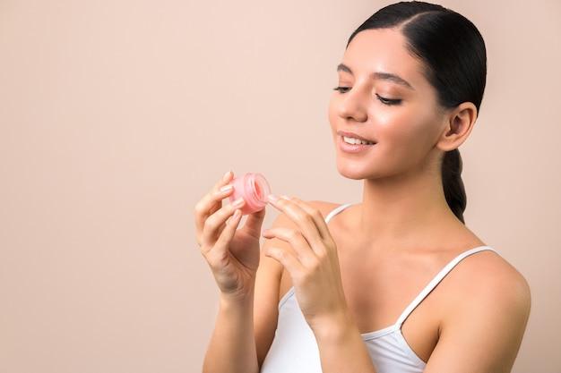 Woman applying lip mask on lips