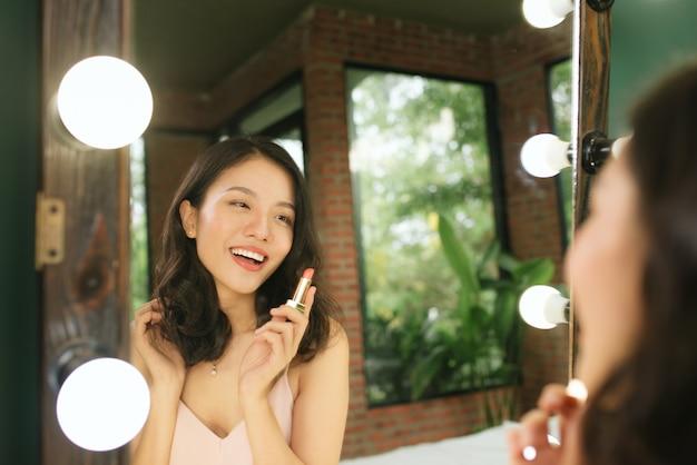 거울을 보고 립스틱을 바르는 여자. 아름다운 소녀는 화장을 한다