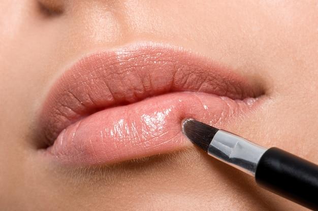 브러시-근접 촬영으로 입술에 립스틱을 적용하는 여자