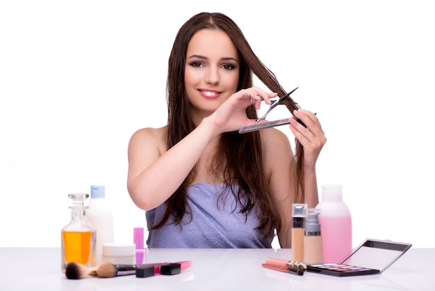 Woman applying make-up isolated on white