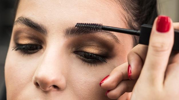 Женщина, применяя макияж на модели