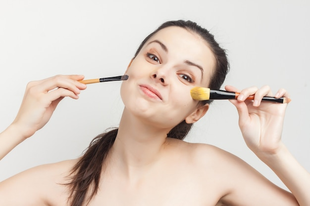 Woman applying makeup brush on face skin care.