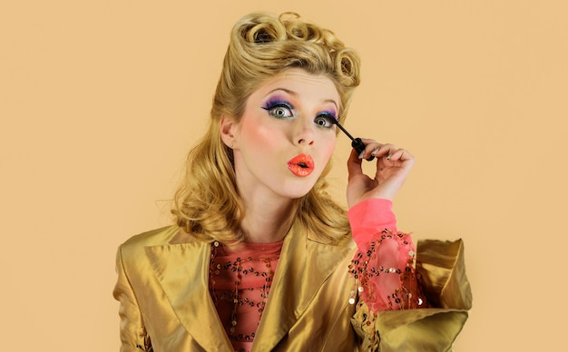 化粧ブラシ、完璧なメイク、化粧品、顔、創造的なメイクでまつげにマスカラを適用する女性。