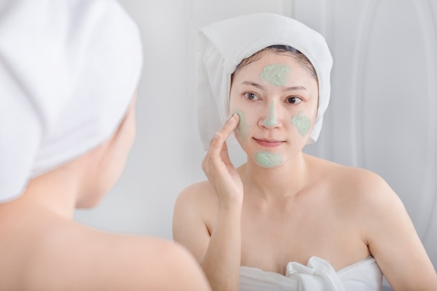 Woman applying mask on her face and looking in the mirror Premium Photo
