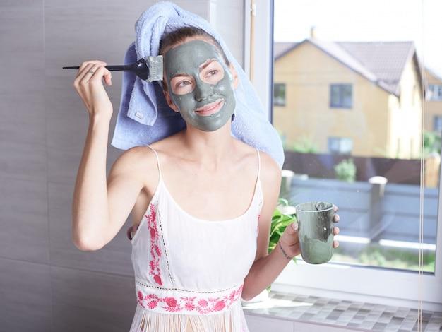 욕실 거울을보고 얼굴에 마스크 보습 스킨 크림을 적용하는 여자. 그녀의 안색 레이어 로션을 돌보는 소녀. 스킨 케어 스파 트리트먼트.