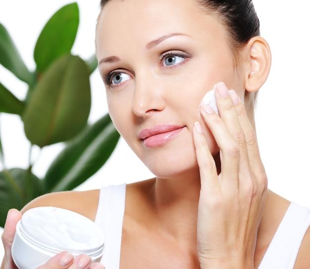 Женщина, применяющая увлажняющий крем для красивого лица