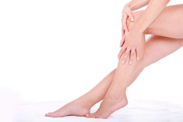 Woman applying moisturizer cream on the legs