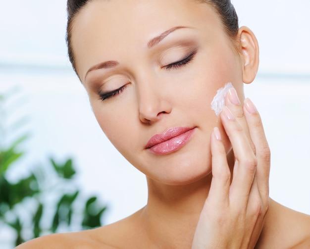 Женщина наносит увлажняющий крем на щеку