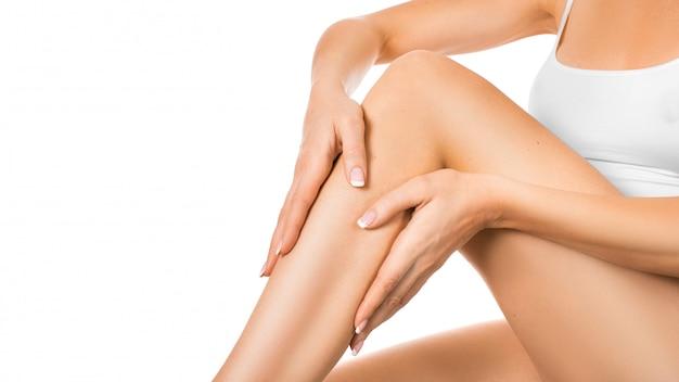 彼女の完璧な脚に保湿剤を適用する女性。肌と体のケアの概念。