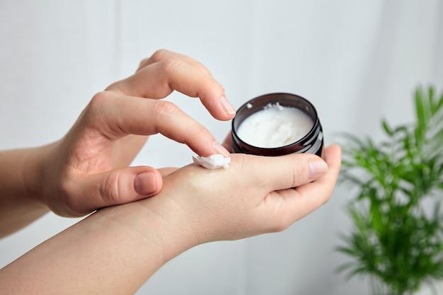 Женщина наносит увлажняющий крем на кожу рук