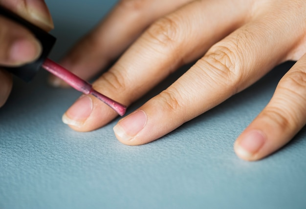 Woman applying nail polish on her nails