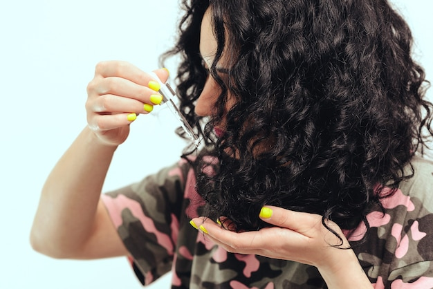 Woman applying natural oil on the tips of her curly hair