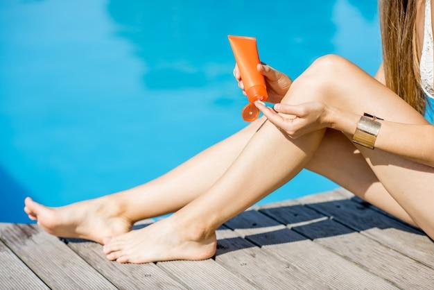 青い水の背景の盆地の近くに座っている足の日焼け止めローションを適用する女性。日焼け止めソーラークリームuv保護コンセプト