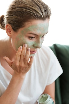 Woman applying organic facial mask