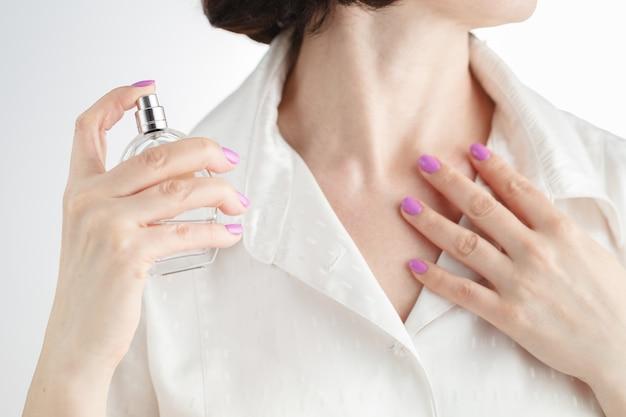 彼女の首に香水を適用する女性