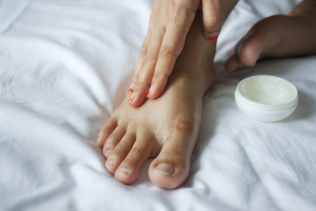 ベッドの上の足にワセリンを塗る女性