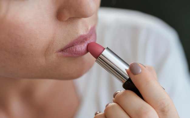 Woman applying pink lipstick on her lips