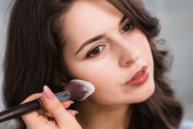 Woman applying powder on face
