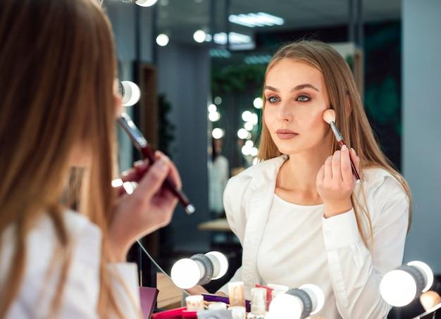 鏡の中の粉を適用する女性