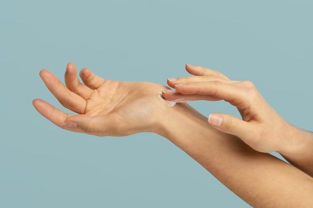 寒い季節や暖房の時期に手の乾燥肌に保護クリームを塗る女性