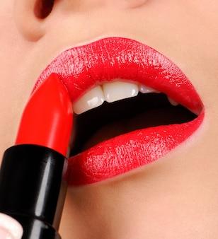 赤い光沢の口紅を適用する女性。