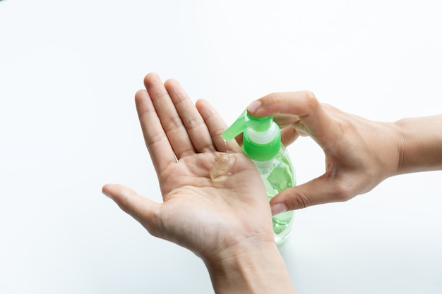 Woman applying sanitizer gel onto her hand for protection against infectious virus, bacteria and germs in white surface. protection concept.