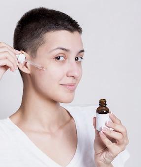 Woman applying serrum on face