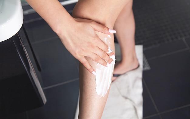 足にシェービングクリームを塗る女性。脱毛の概念