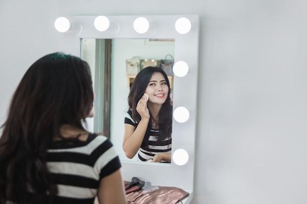 いくつかの化粧パウダーを適用する女性