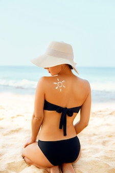 Woman applying sun cream creme on tanned  shoulder in form of the sun.