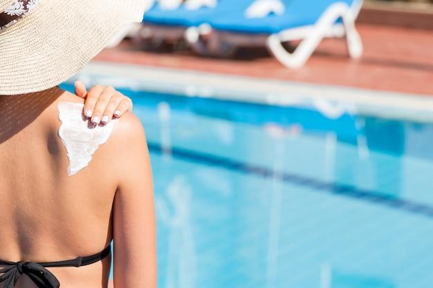 Woman applying sun cream on her shoulder