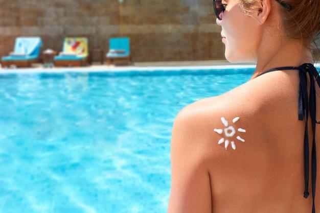 태양의 형태로 검게 그을린 된 어깨에 썬 크림을 적용하는 여자. 썬 프로텍션. 썬 크림. 피부 및 바디 케어. 피부에 자외선 차단제를 사용하는 소녀.