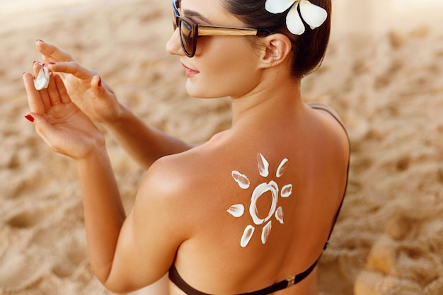 Woman applying sun cream  on tanned shoulder in form of the sun