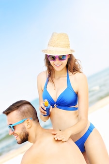 Woman applying sunscreen on the back of her man at the beach