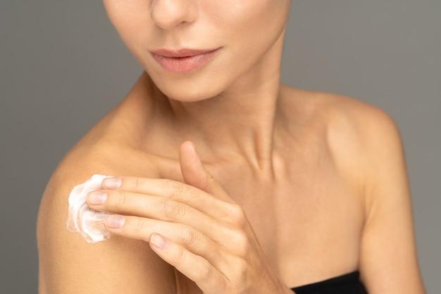 어깨에 완벽한 수분 피부에 선 스크린 크림 또는 화장품 보습 로션을 바르는 여성