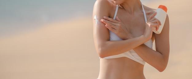 Женщина, применяющая солнцезащитный крем в своем теле на пляже.