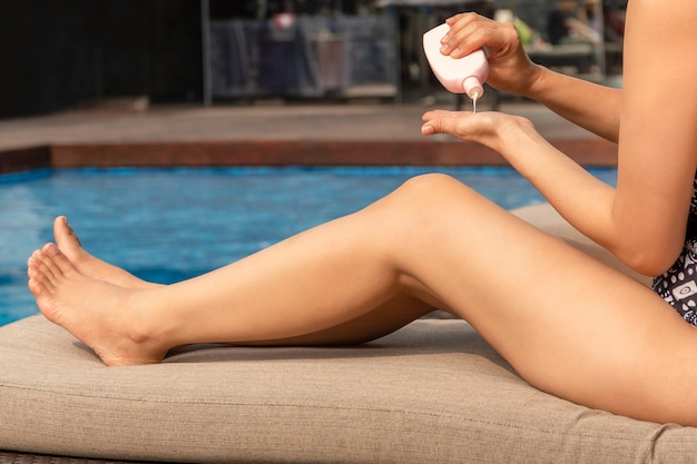Woman applying sunscreen lotion on her hand by swimming pool on vacation.