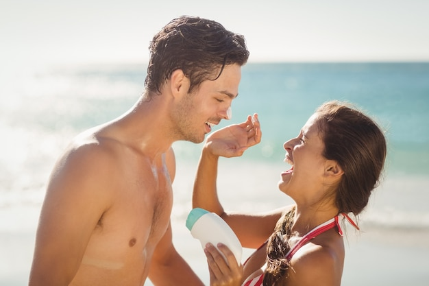 Woman applying sunscreen lotion on mans face