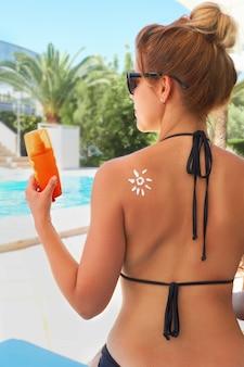 수영장에서 태양의 형태로 검게 그을린 어깨에 자외선 차단제를 적용하는 여자. 피부 관리. 바디 썬 프로텍션 썬 크림. 여성 지주 선탠 로션