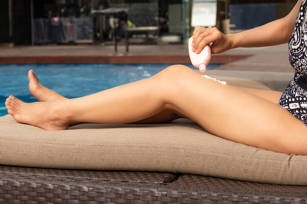 Woman applying sunscreen protection on her legs by swimming pool.