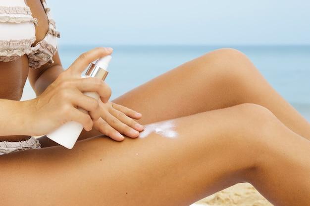 일광욕하기 전에 그녀의 몸에 자외선 차단제 스프레이를 적용하는 여자