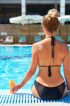 Woman  applying sunscreen on  tanned  shoulder in form of the sun  by pool. skin care. body sun protection sun cream. bikini  woman smear  moisturizing lotion on back. female holding suntan lotion