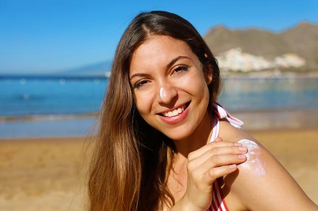 ビーチで彼女の鼻と肩に日焼け止めクリームを適用する女性