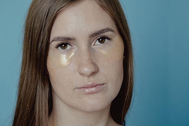 눈 패치, 다크 서클 및 붓기를 위한 아이 마스크 아래에 적용하는 여성. 그녀의 눈 아래에 황금 콜라겐 패치를 적용하는 예쁜 여자. 여자 페이셜 트리트먼트 . 미용, 미용 및 스파