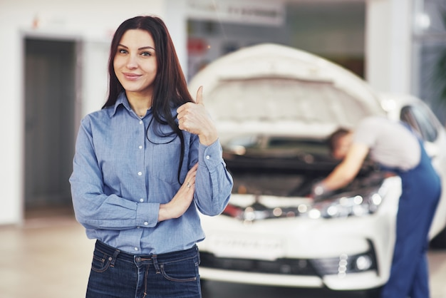 The woman approves the work done by the client. the mechanic works under the hood of the car