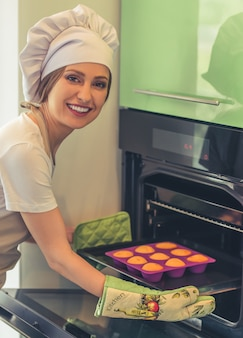 Woman in apron and cooking hat is looking at camera.