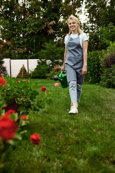 Woman in apron and gloves holds watering can in the garden. female gardener takes care of plants outdoor, gardening hobby, florist lifestyle