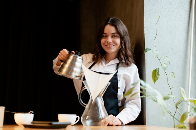 Woman in apron posing with coffee pot