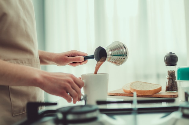 Woman in apron prepare hot tasty turkish coffee from cezve for breakfast at kitchen at home.