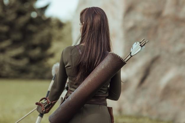 Женщина-лучница со стрелами на спине, стоит спиной к зрителю на размытом фоне, крупным планом